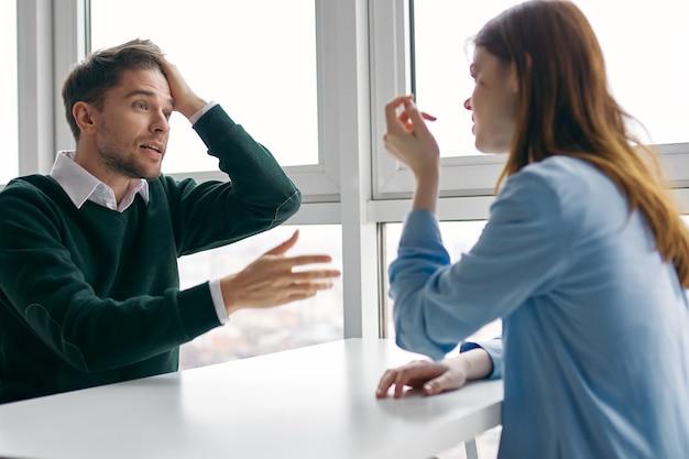Een man en een vrouw zitten aan tafel en communiceren tegenover elkaar bij het raam