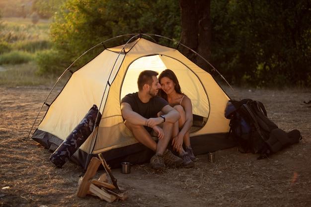 Een man en een vrouw zitten in een tent bij zonsondergang. huwelijksreis tijdens de wandeling