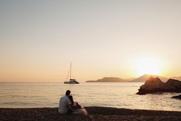 Een man en een vrouw zitten knuffelend op de oever van een kalme zee en kijken naar het zeilschip