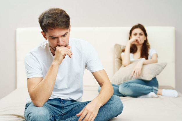 Een man en een vrouw zitten op het bed en praten over een relatie, een echte ruzie