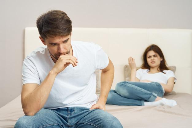 Een man en een vrouw zitten op het bed en praten over een relatie