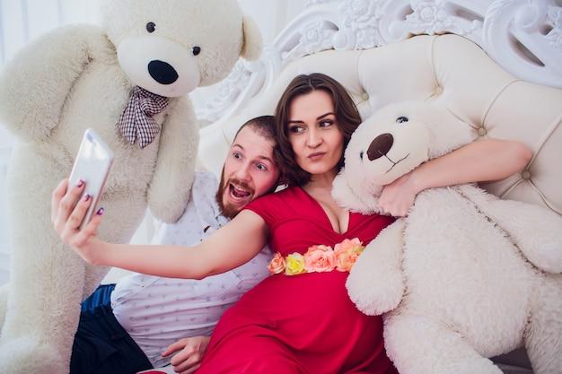 Een man en een zwangere vrouw maken selfie zittend op de bank. ze houden van elkaar. ze zijn thuis.