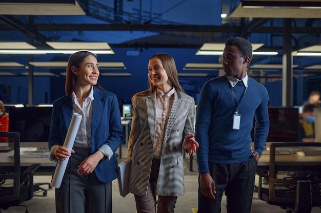 Een man en twee vrouwen in nachtkantoor. glimlachende mannelijke en vrouwelijke werknemers, donker zakencentrum interieur, moderne werkplek modern