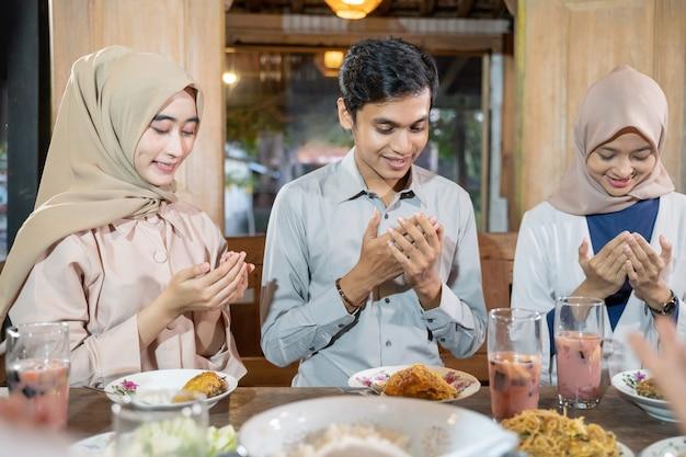 Een man en twee vrouwen in sluier bidden samen voor het eten
