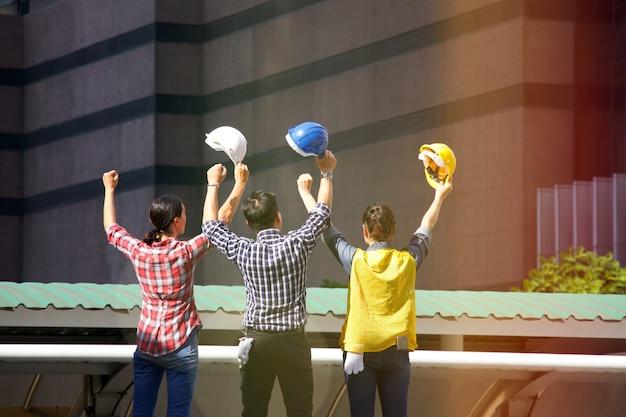 Een man en twee werkende vrouwen werken samen op de bouwplaats