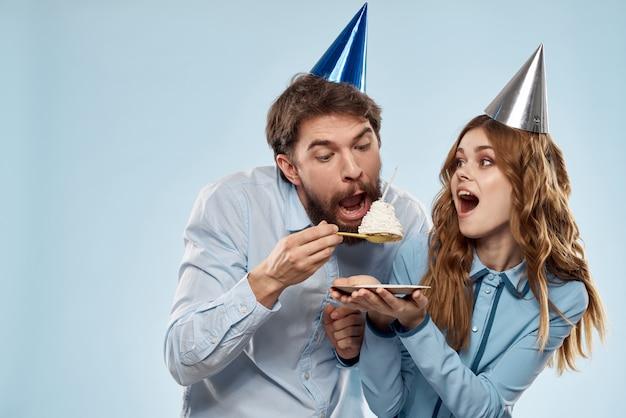Een man en vrouw met een cupcake en een kaars in feestelijke caps