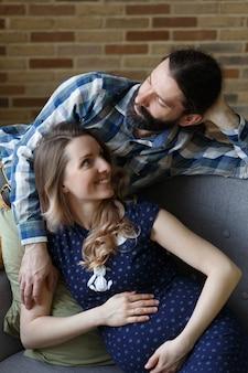 Een man en zijn zwangere vrouw poseren thuis op een bank