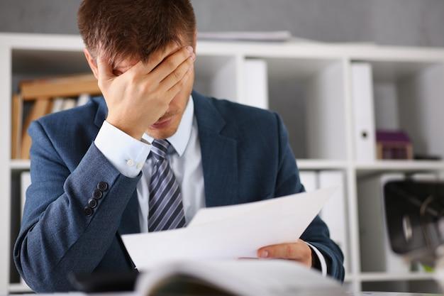 Een man ervaart stress en hoofdpijn op de werkplek