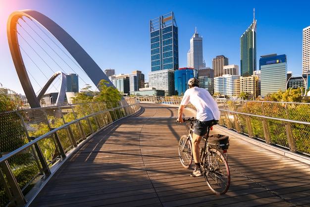 Een man fietsen op een elizabeth bridge in de stad perth