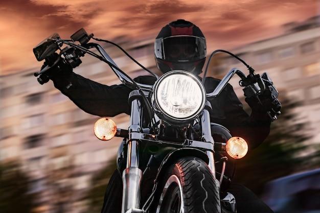 Een man fietser op een motorfiets in de avond op een stadsstraat. detailopname. nacht motorrijder.