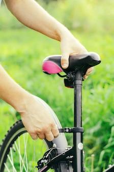 Een man gaat rechtop staan en repareert de stoel van een mountainbike op een bosweg. fietsstoring, voertuigreparatie.