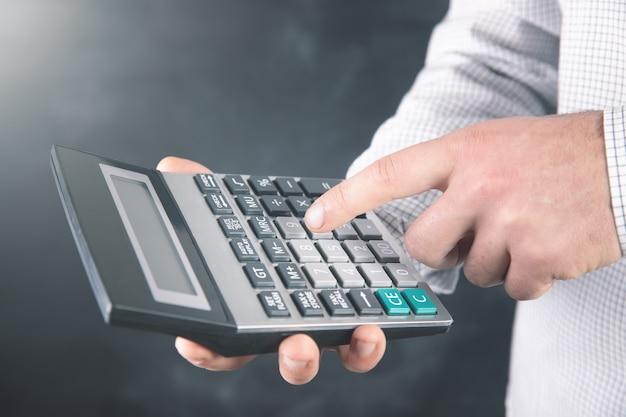 Een man gebruikt een rekenmachine.