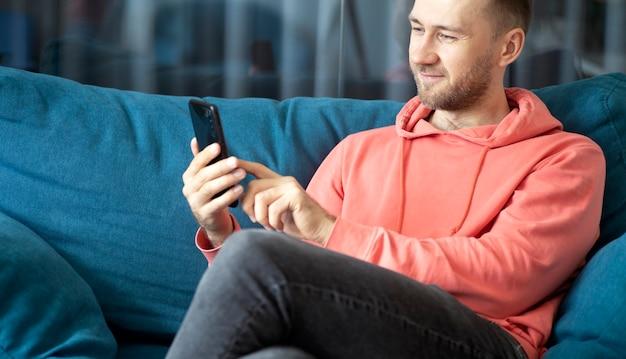 Een man gebruikt een smartphone op zijn thuisbank terwijl hij thuis ontspant, toepassingen noemen internetconcept foto's van hoge kwaliteit