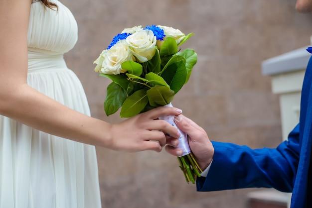 Een man geeft een boeket aan een zwangere vrouw