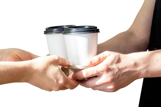 Een man geeft een dienblad met papieren wegwerpkoffiebekers aan een vrouw