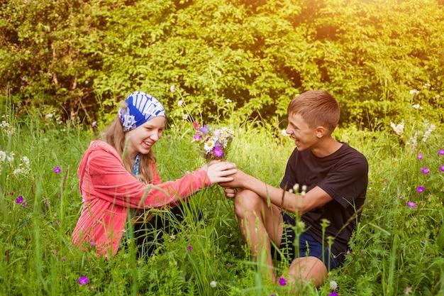 Een man geeft een meisje een boeket wilde bloemen zittend in een weiland