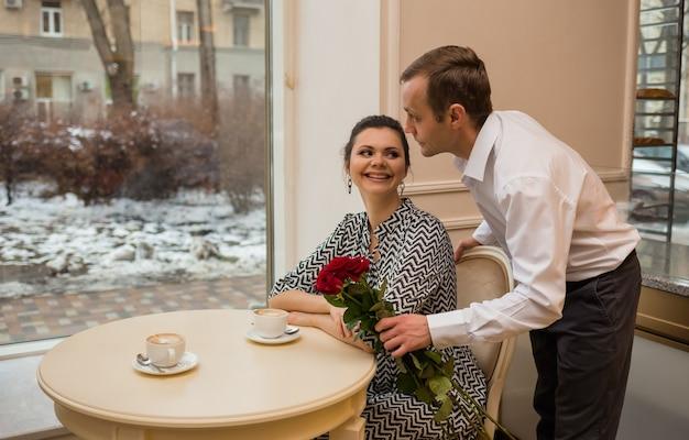 Een man geeft een vrouw een boeket rode rozen in een café