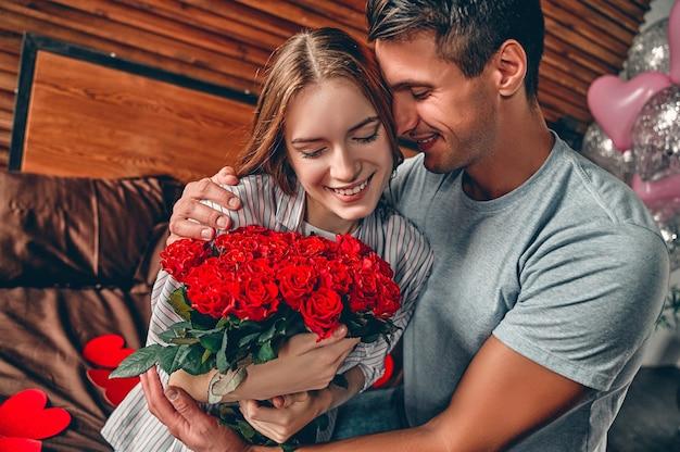 Een man geeft een vrouw een boeket rode rozen. op het bed zit een stel met hartvormige confetti.