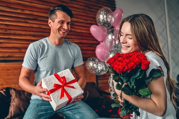 Een man geeft een vrouw een cadeau en rode rozen. op het bed zit een stel met hartvormige confetti.