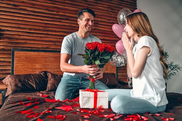 Een man geeft een vrouw een cadeau en rode rozen