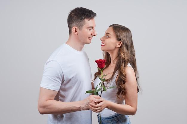 Een man geeft een vrouw een rode roos