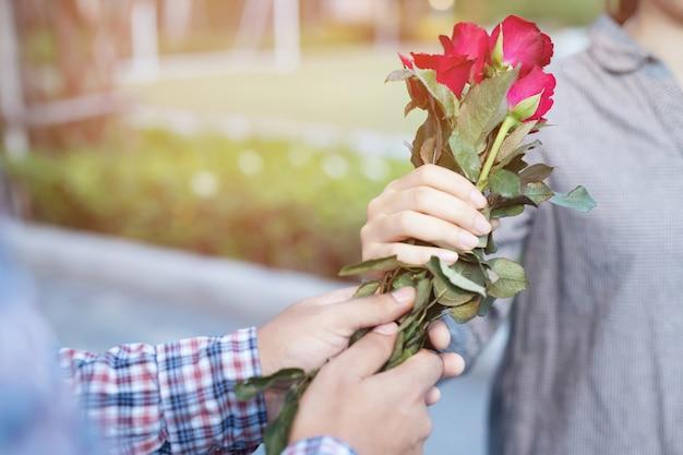 Een man geeft rode rozen aan zijn geliefde op valentijnsdag