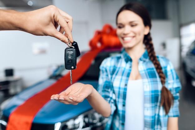 Een man geeft zijn vriendin de sleutels van een nieuwe auto.