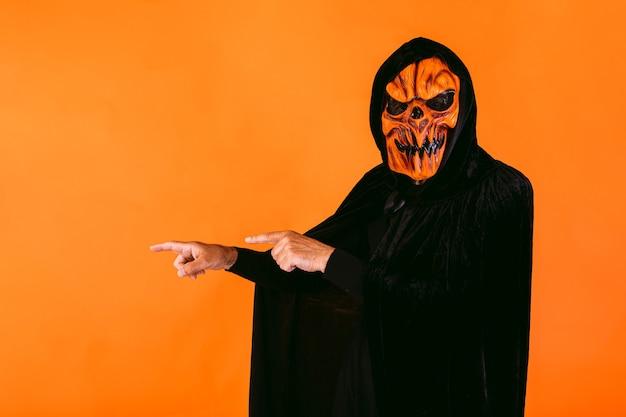 Een man gekleed in een latex pompoenmasker en een fluwelen cape met capuchon wijst zijn vingers naar links waar er kopieerruimte is. halloween en dagen van het dode concept.