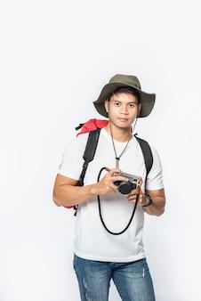 Een man gekleed om te reizen met een hoed en een camera
