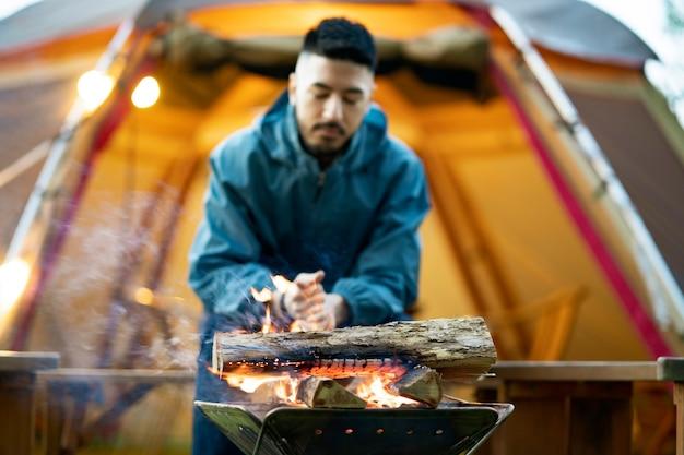 Een man geniet van een kampvuur voor de tent