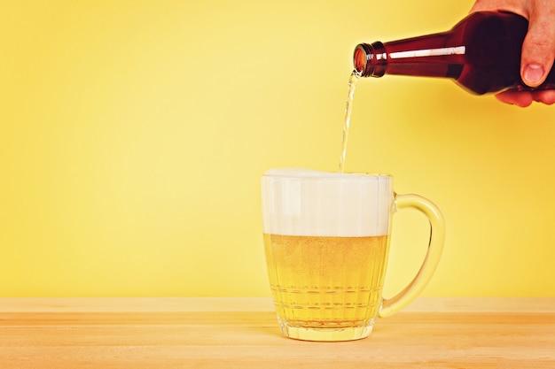 Een man giet bier in een mok van een fles op een gele achtergrond op een houten tafel. ruimte kopiëren.