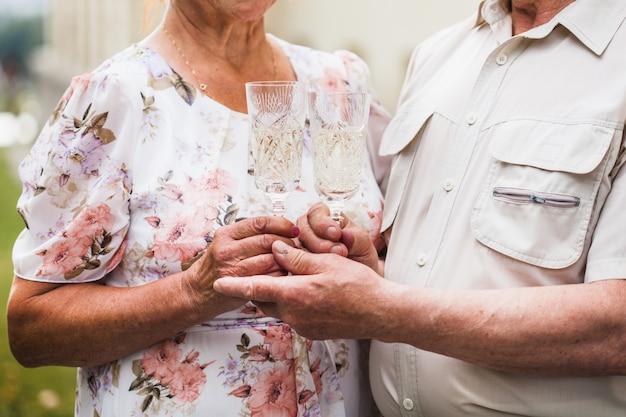 Een man giet champagne of witte wijn in een glas van zijn geliefde vrouw, alcoholische dranken, verjaardagsviering, verjaardag