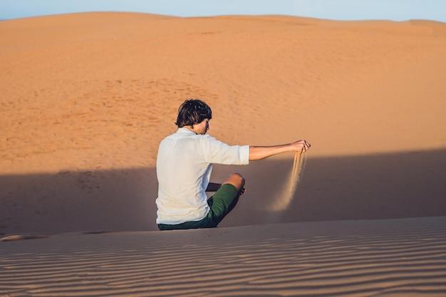 Een man giet zand in de woestijn. zand door de vingers van het concept