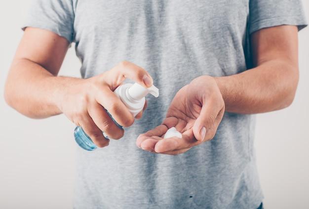 Een man gieten vloeibare zeep aan zijn hand op witte achtergrond in grijs t-shirt.