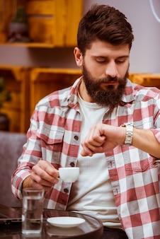 Een man ging uit voor een koffiepauze en drinkt koffie.