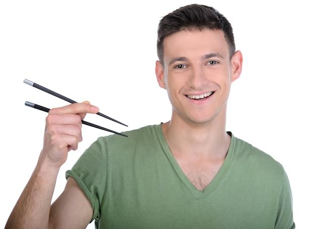 Een man glimlacht en houdt sushistokken in zijn handen.