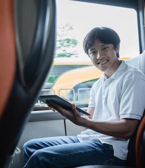 Een man glimlacht terwijl hij een tablet gebruikt terwijl hij in een bus zit