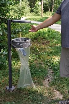 Een man gooit een ijzeren blik pepsi-cola in de vuilnisbak