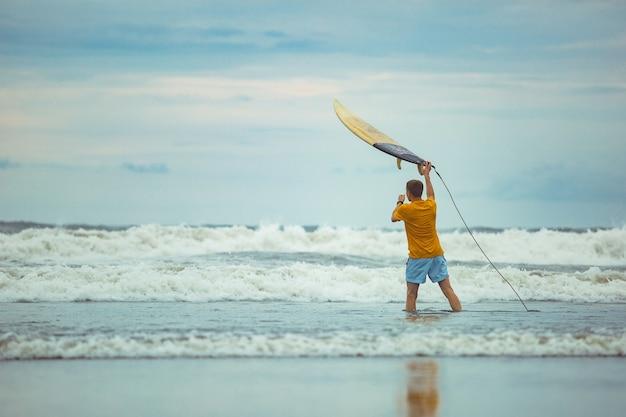 Een man gooit een surfplank naar boven.