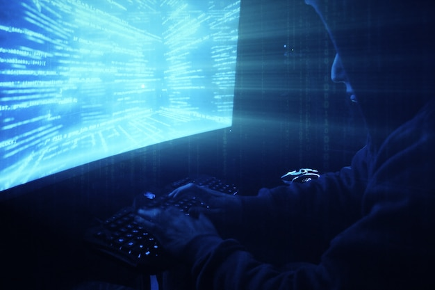 Een man hacker in een capuchon in een donkere kamer