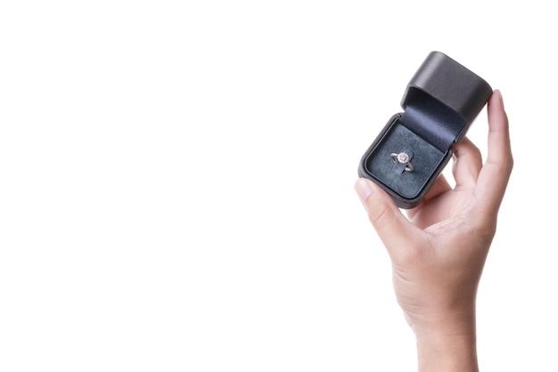 Een man hand met doos met ring voor huwelijksaanzoek