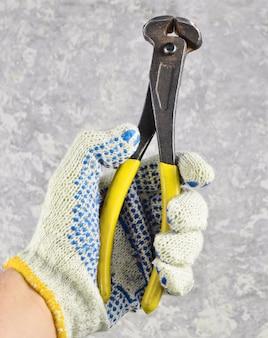 Een man hand met handschoenen houdt metaaltangen tegen een grijze concrete achtergrond