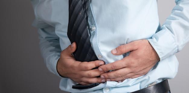 Een man heeft buikpijn op een grijs oppervlak