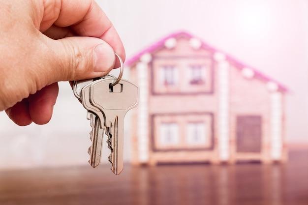 Een man heeft de sleutels van een nieuw huis