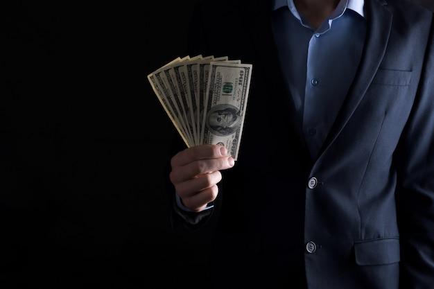 Een man heeft dollars in zijn handen. een man telt dollars.