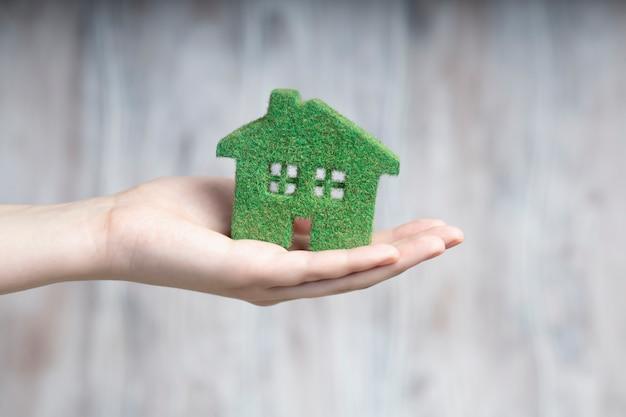 Een man heeft een eco-huis in zijn handen.