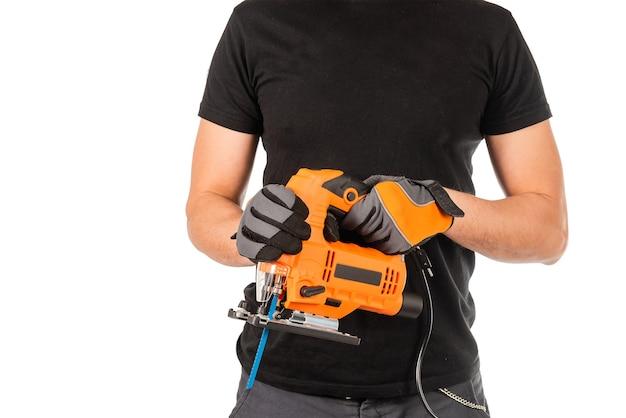 Een man heeft een elektrische decoupeerzaag in zijn handen