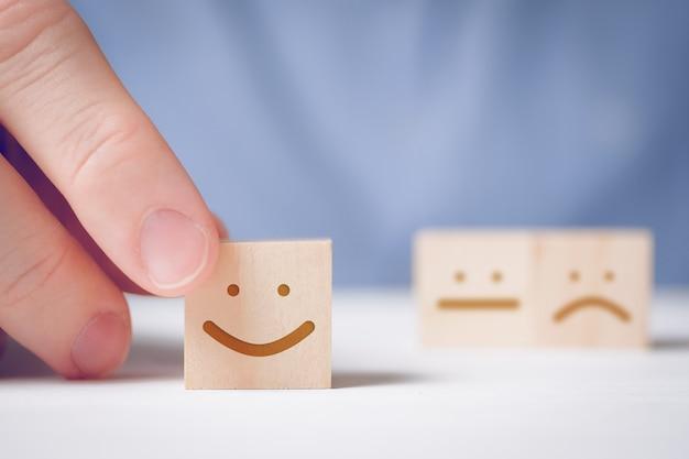 Een man heeft een houten kubus met een positief gezicht op een neutraal en negatief. voor het evalueren van een actie of resource.