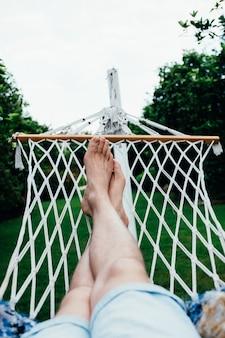 Een man heeft een rust liggend op een hangmat in tropische tuin