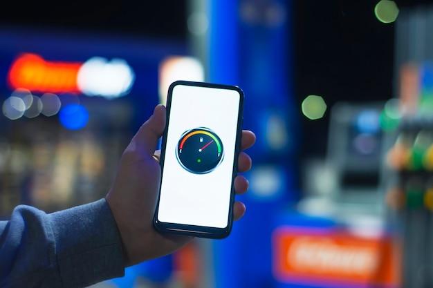 Een man heeft een smartphone met een digitale brandstofmeter op het scherm